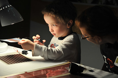 A visitor at the Museum of Science NanoDays explores solar panels developed by local industry partner, Konarka.